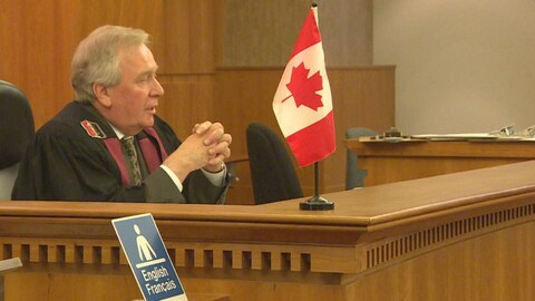 Un homme est assis à un bureau devant un drapeau canadien et un panneau disant english / français.