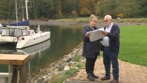 Un homme et une femme regardent des feuilles blanches debout près de l'eau où il y a un voilier