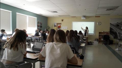Des élèves écoutent la professeure.