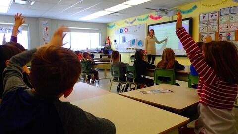 À l'école Saint-Louis à L'Assomption on a dû ajouter 4 classes en préfabriqué. Sur la photo des élèves, de dos, lèvent la main pour répondre à une question que vient de poser l'enseignante qui leur fait face.