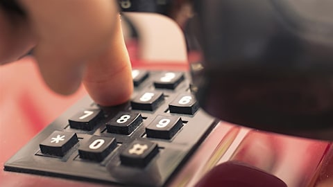 Une personne compose un numéro de téléphone.