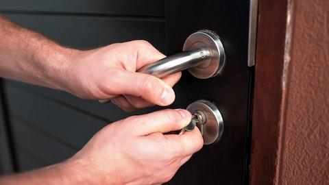 Un homme ouvre une porte avec une clé.