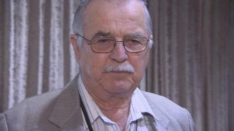 Portrait d'un homme aux cheveux et à la moustache gris, qui porte des lunettes.