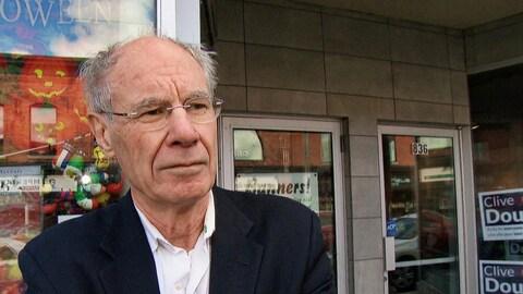 Un homme portant des lunettes devant son bureau de campagne.