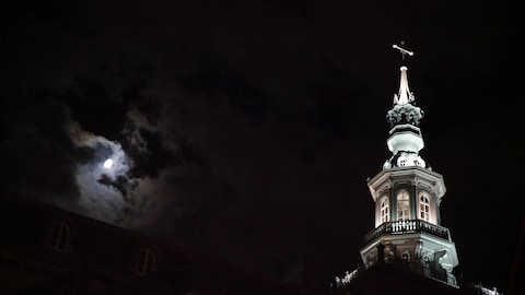 Le clocher du Collège François-de-Laval par une froide nuit de début novembre. La lune brille en arrière plan du clocher, accompagnée de quelques nuages.