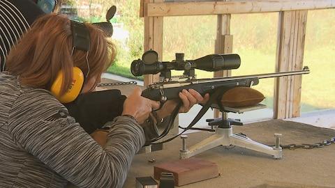 Femme qui vise avec une arme à feu