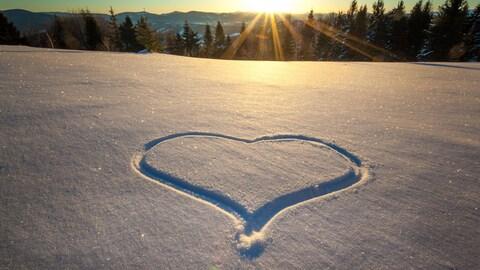 Un cœur dessiné dans la neige.