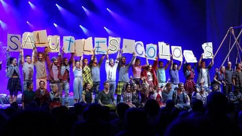 Les artistes tiennent dans leurs mains des lettres qui forment le message «Salut les Colocs»