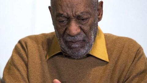 Un Noir chauve à la barbe grisonnante regarde vers le sol et semble triste.