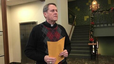 Un homme est debout dans un hall d'entrée. Il porte une enveloppe dans les mains