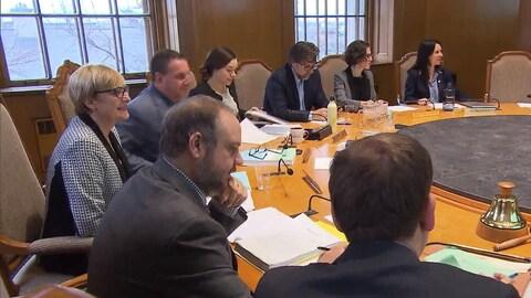 Les membres du comité exécutif sont assis autour d'une grande table ronde.