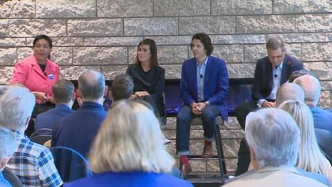 Deux femmes et deux hommes sont assis sur une estrade. Ils s'adressent tous les quatre à des gens dans une salle.