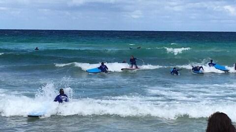 Des jeunes font du surf dans l'océan.