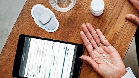 Une photo prise du dessus dans laquelle on peut voir la main d'une personne tenant un petit comprimé blanc et une table sur laquelle sont déposés un iPad, un timbre médical, un verre d'eau et un flacon de médicaments.