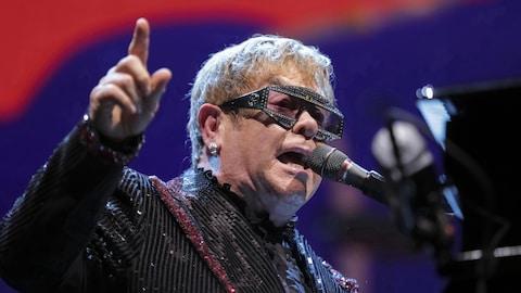 Elton John chante dans un micro, assis sur un piano, et lève sa main droite.
