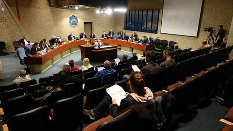 Élus assis à leur siège de conseilles et gens du public face à eux dans les sièges.