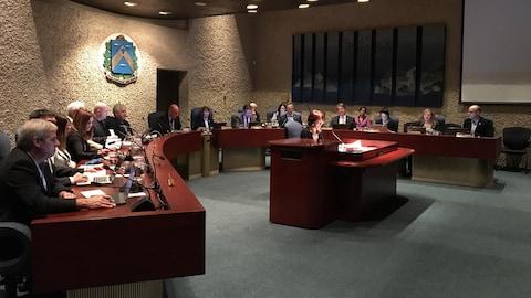 Les conseillers et le maire de Trois-Rivières, assis autour de la table de la salle du conseil, font face au public qu'on ne voit pas. La greffière de la Ville assise devant eux, faisant aussi face au public dans la salle.