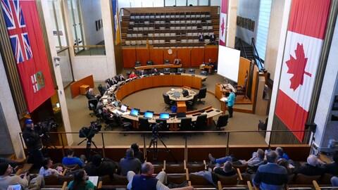 la salle du conseil municipal vue de haut. Tout en bas de la photo, la table en cercle autour de laquelle les conseillers sont assis, et de chaque côté des gradins avec des gens asiss dans les sièges.
