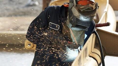 Un travailleur utiliser une pince dans une main et de l'autre une soudeuse. Il travaille à joindre deux pièces ensemble.