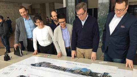 Jim Watson et des conseillers municipaux devant une table où est présenté un plan de la rue Sparks.