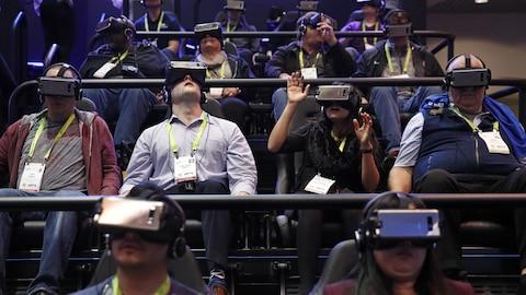 Des personnes assises dans des gradins en train de réagir à une présentation en réalité virtuelle.