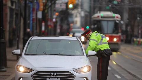 Un policier parle à un automobiliste qu'il a arrêté. Un tramway arrive en arrière-plan.