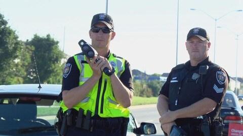 Le policier tient un radar dans ses mains le long d'une rue d'Ottawa