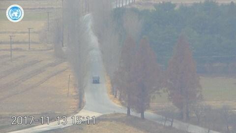 Une jeep foncée vue de loin descend une route, qui se divise plus bas en deux branches. Des arbres se trouvent le long de la route et un petit brouillard semble s'être installé.