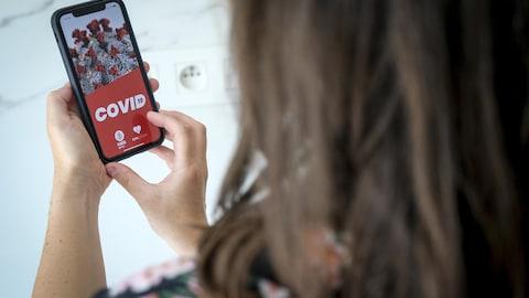 Une femme manipule un téléphone intelligent avec une application de traçage de la COVID-19 à l'écran.