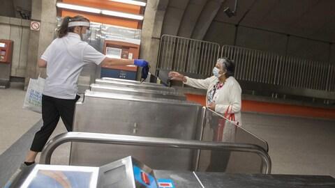 Une jeune employée de la STM tend un masque à une dame. Photo prise au métro Langelier, à Montréal, Québec, Canada.  Le 25 Mai 2020 2020/05/25.