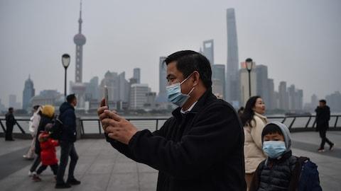 Un homme portant un masque respiratoire fait un égoportrait à Shanghai.