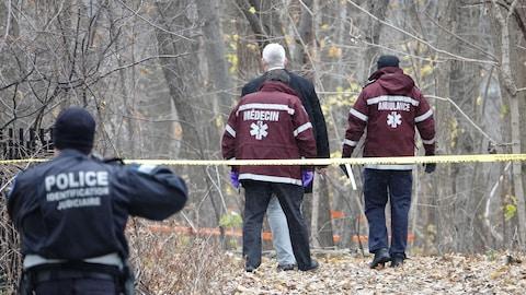 Un médecin, un ambulancier et des policiers arpentent une scène de crime à L'Île-des-Soeurs, à Montréal.