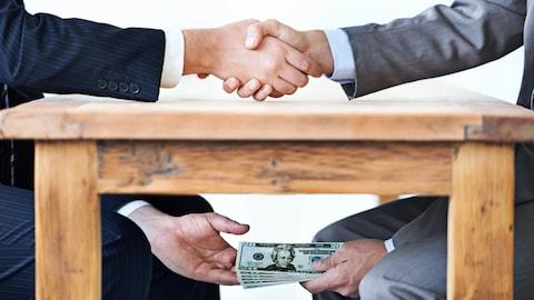 Mise en scène montrant deux hommes se serrant la main au-dessus de la table et échangeant une liasse de billets de banque en dessous de la table.