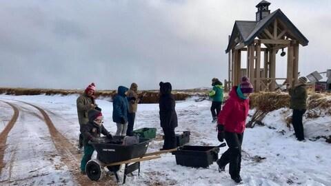 Un groupe de Madelinots ramassent des déchets sur une plage à l'aide de bacs et d'une brouette.