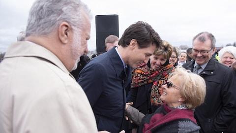 Justin Trudeau prend dans ses bras Colette Roy-Laroche pendant que Philippe Couillard regarde la scène.