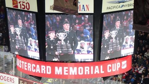 La trophée de la Coupe Memorial fait son entrée dans le centre WFCU de Windsor, porté par un militaire des Forces canadiennes