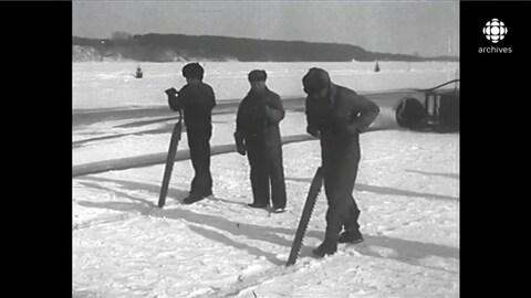 Deux coupeurs de glace équipés de longues scies taillant la surface de glace enneigée du fleuve. Un homme armé d'un long pic les accompagne.