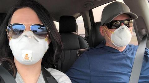 Un couple dans une voiture avec des masques blancs pour se protéger de la fumée.