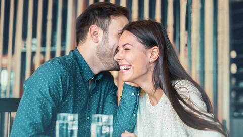Un homme chicotte à l'oreille d'une femme en train de rire.