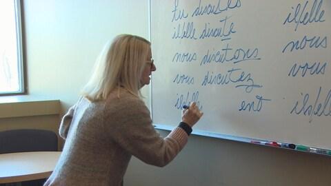 Une professeure de français devant un tableau blanc.