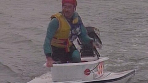 Un homme qui porte une veste de sauvetage jaune et un casque de hockey rouge est dans une baignoire équipée d'un moteur qui lui sert de bateau dans l'eau.