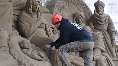 Un artiste sculptant la crèche de sable du Vatican sur la place Saint-Pierre.