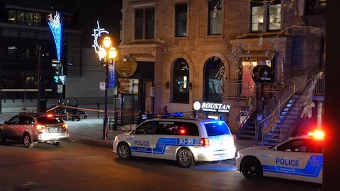 Deux voitures de police au coin de la rue Crescent et du boulevard De Maisonneuve.