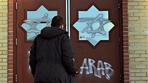 Une homme debout face à des portes fermées sur lesquelles des graffitis ont été inscrits, dont le mot « arab », en anglais.