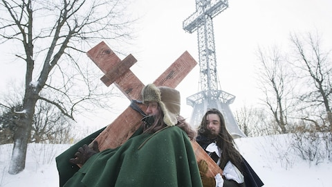 Un homme habillé en Paul de Chomedey traîne une croix de bois sur le sommet du mont Royal.