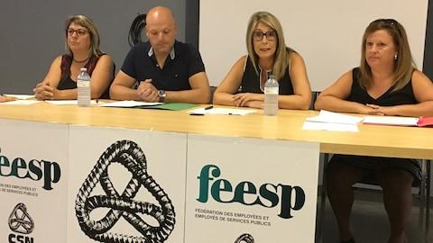 Trois femmes et un homme sont assis, alignés derrière une table, avec des documents et des affiches de la CSN