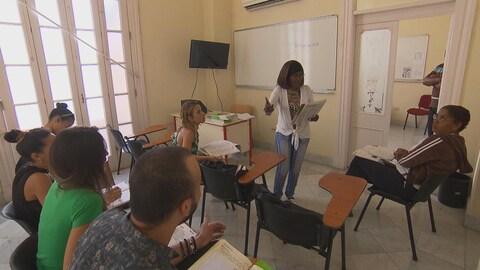 Une professeure donne des cours de français à plusieurs Cubains.