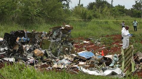 Un membre des services d'urgence se tient près des débris d'un avion s'étant écrasé près de La Havane, faisant 110 morts.