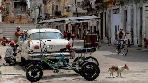 Une voiture et un vélo-taxi sont garés en bordure de la rue, dans un quartier pauvre de La Havane.