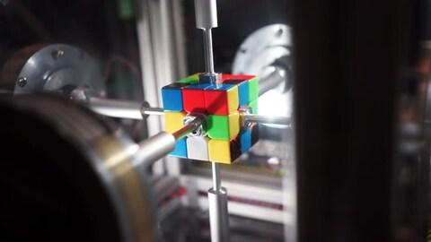 Une capture d'écran montrant un cube de Rubik mélangé enserré par des tiges de métal touchant la tuile centrale de chaque face.